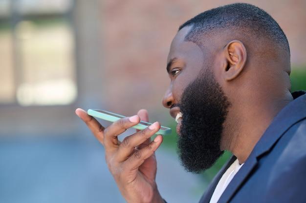 Een man met een donkere huidskleur in een pak die een spraakbericht opneemt