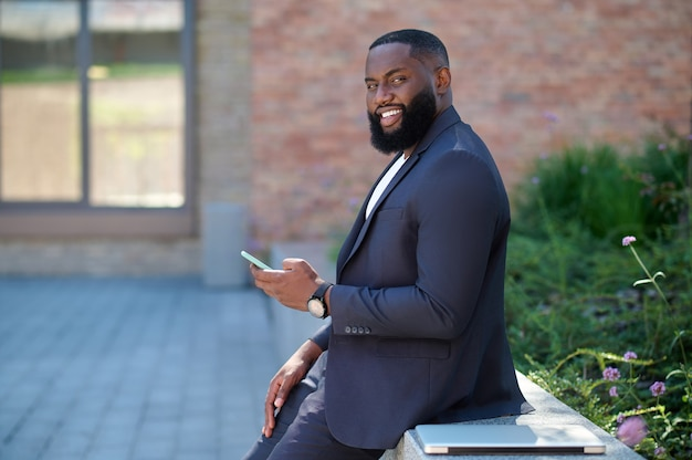 Een man met een donkere huidskleur in een pak met een telefoon in handen