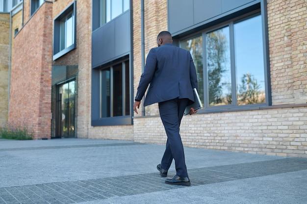 Een man met een donkere huidskleur in een pak op weg naar zijn werk