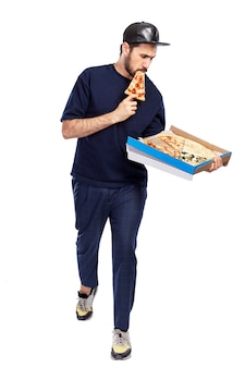 Een man met een doos pizza in zijn handen eet een stuk. de man met de pet en blauwe kleren. voedsellevering. volledige hoogte. geïsoleerd op een witte achtergrond. verticaal.