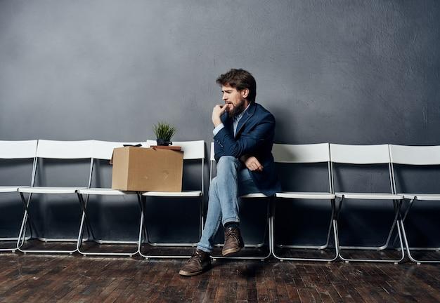 Een man met een doos zit op een stoel met dingen, documenten