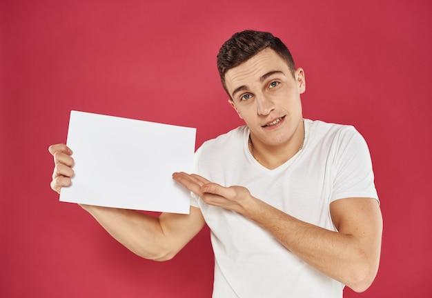 Een man met een flyer in zijn handen op een rode achtergrond in een wit t-shirt bijgesneden weergave