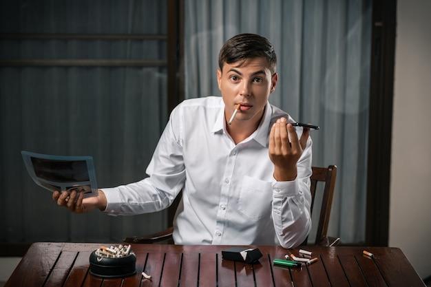 Een man met een foto van een longfoto, zittend aan een tafel met een asbak erop