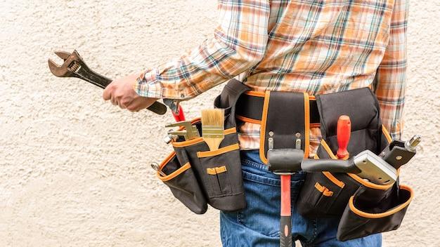 Een man met een gereedschapsriem, die een moersleutel vasthoudt.