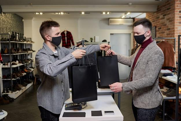 Een man met een gezichtsmasker om de verspreiding van het coronavirus te voorkomen, haalt zijn aankopen bij een verkoper in een kledingwinkel. een mannelijke winkelbediende geeft papieren zakken met kleding aan een klant in een boetiek.