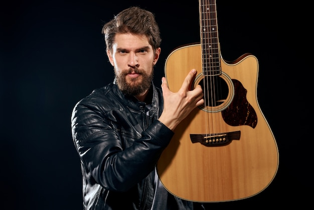 Een man met een gitaar in zijn handen lederen jas muziekprestaties rockster moderne stijl donkere achtergrond. hoge kwaliteit foto