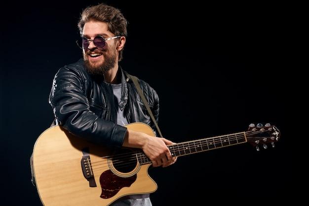 Een man met een gitaar in zijn handen leren jas muziek prestatie rockster moderne stijl donker