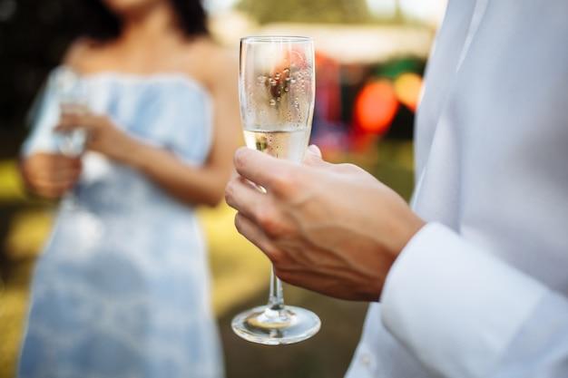 Een man met een glas champagne in zijn handen op een gezelschap van vierende mensen. bruiloft, verjaardag, jubileum.
