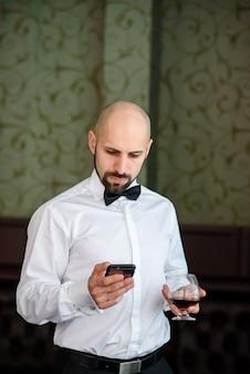 Een man met een glas cognac die naar de telefoon kijkt