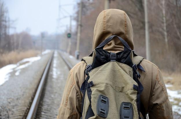 Een man met een grote rugzak gaat vooruit op de spoorweg