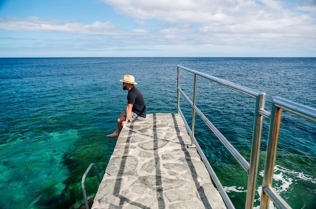 Een man met een hoed, toerist, geniet in de zomer van het uitzicht op de zee vanaf een stenen wandeling langs de kust