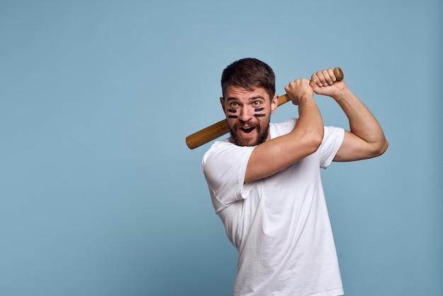 Een man met een houten knuppel en zwarte lijnen op zijn gezicht blauw wit t-shirt als achtergrond