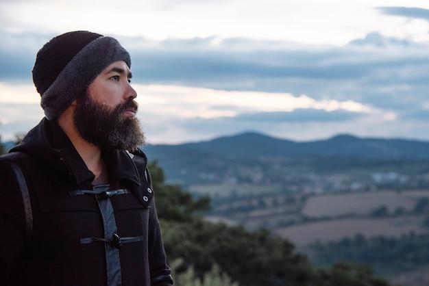 Een man met een houthakkersbaard in een zwarte regenjas kijkt naar de horizon richting de bergen op de top van een bos