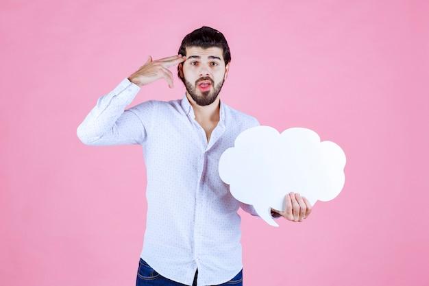 Een man met een ideeënbord in de vorm van een wolk ziet er attent uit.