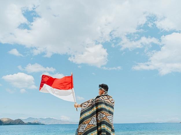 Een man met een indonesische traditionele doek genaamd kain songket die de indonesische vlag zwaait onder de blauwe lucht