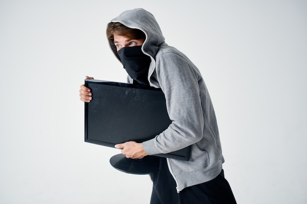 Een man met een kap in een masker steelt een technische computer
