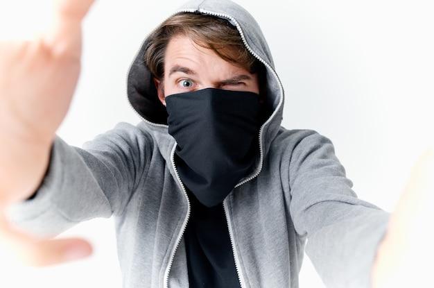 Een man met een kap verbergt zijn gezicht in een masker pest anonimiteit. hoge kwaliteit foto