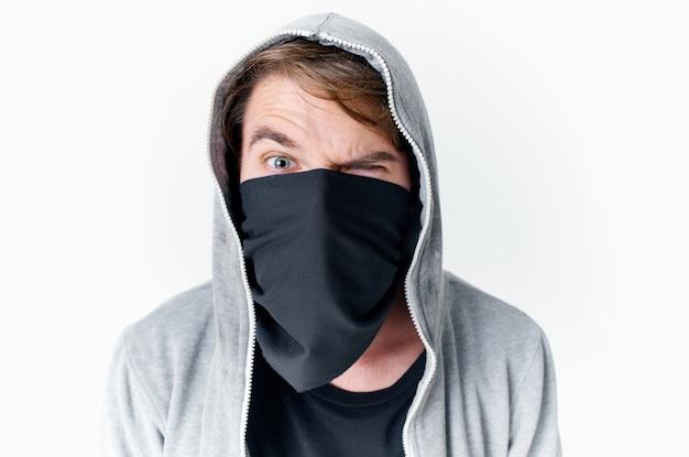 Een man met een kap verbergt zijn gezicht in een masker pest anonimiteit