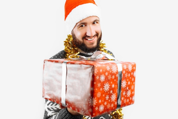 Een man met een kerstcadeau in zijn handen in de studio op een witte achtergrond cadeau close-up geeft een kerstcadeau