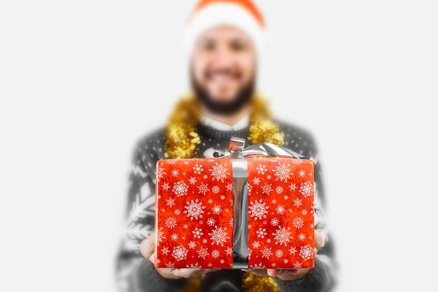 Een man met een kerstcadeau in zijn handen in de studio op een witte achtergrond cadeau close-up