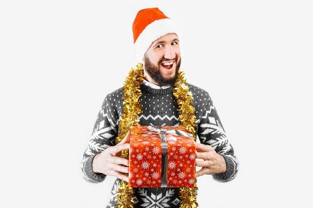 Een man met een kerstcadeau in zijn handen in de studio op een witte achtergrond geeft een kerstcadeau