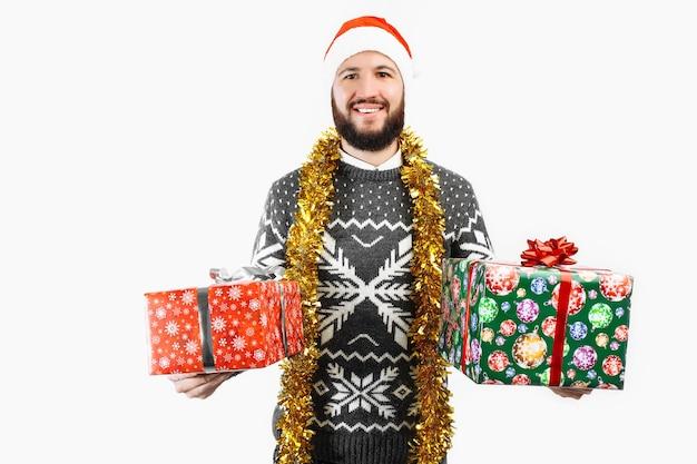 Een man met een kerstcadeau in zijn handen in de studio op een witte achtergrond kiest een cadeau
