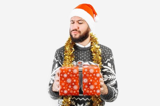 Een man met een kerstcadeau in zijn handen in de studio op een witte achtergrond
