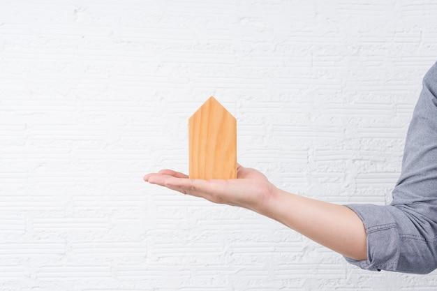 Een man met een klein houten huis op zijn hand met een witte muur.