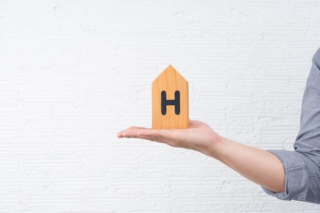Een man met een klein houten huisje met de letter h op zijn hand met een witte muur.