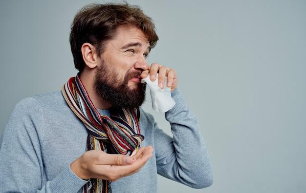 Een man met een koude veegt zijn neus af met een zakdoek gezondheidsproblemen pillen geneeskunde
