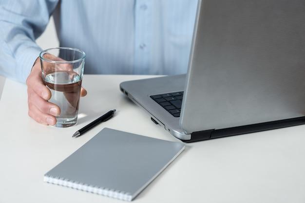 Een man met een laptop houdt een glas water vast.