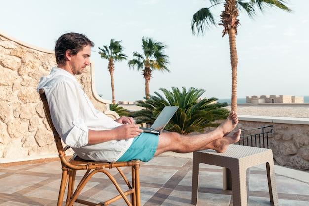 Een man met een laptop in zijn handen rust en werkt als freelancer