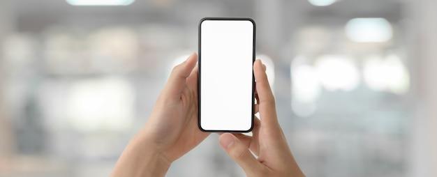 Een man met een leeg scherm smartphone in wazig glazen partitie kantoor