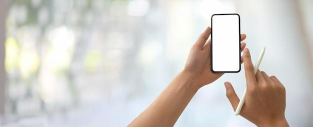 Een man met een leeg scherm smartphone terwijl de stylus in wazig kantoor
