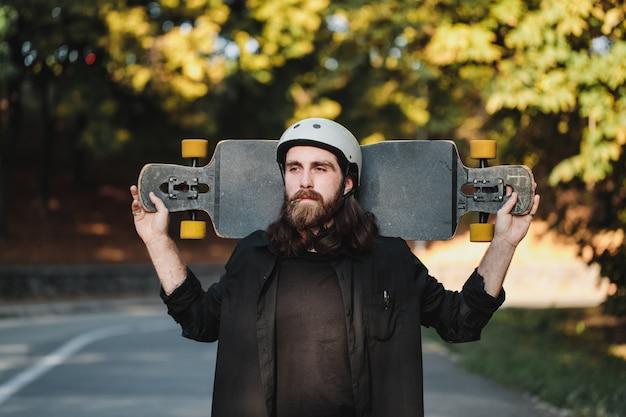 Een man met een longboard rookt een sigaret. een combinatie van sport en lifestyle. hoge kwaliteit foto