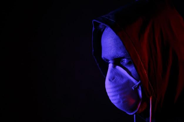 Een man met een masker en een chemisch beschermingspak in rood en blauw licht. strijd tegen het virus. covid-19