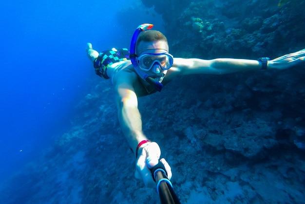 Een man met een masker en snorkel duikt in het blauwe water van de rode zee en fotografeert zichzelf