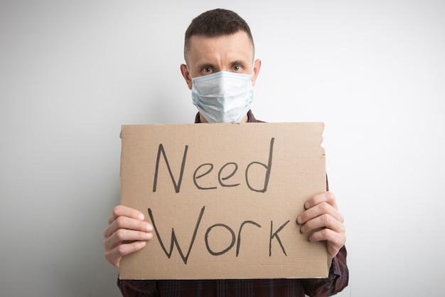 Een man met een masker houdt een poster vast met de woorden ik heb werk nodig. werkloosheid.