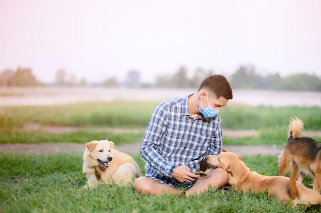 Een man met een masker, zittend spelen met een hond op het gazon. een man blijft thuis spelen met de hond.