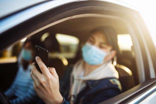 Een man met een medisch masker houdt een mobiele telefoon in zijn hand tijdens het autorijden