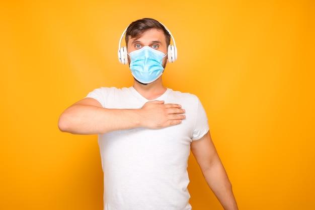 Een man met een medisch masker op zijn gezicht en een muzikale koptelefoon toont verschillende gebaren.