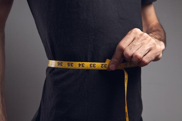 Een man met een meetlint meet de omtrek van de buik