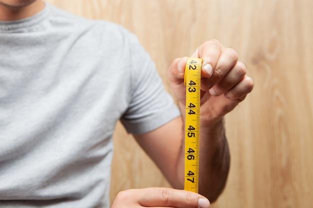 Een man met een meetlint op een houten ondergrond