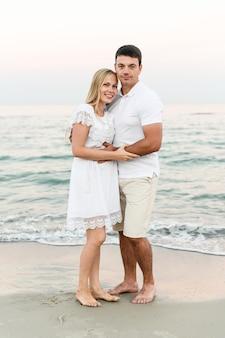 Een man met een meisje in zomerkleren loopt langs de oceaan. man en vrouw bij een romantische zonsondergang van de dag bij de zee.