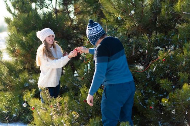 Een man met een meisje siert een groene kerstboom op straat in de winter in het bos met decoratief speelgoed en slingers. kerstboomdecoraties