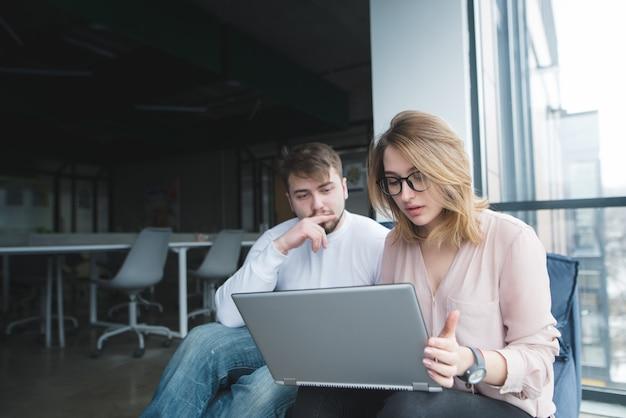 Een man met een meisje zit in het kantoor op de bank en kijken naar de laptop.