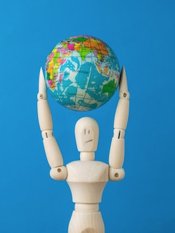 Een man met een model van de wereldbol boven zijn hoofd op een blauwe achtergrond. dag van de aarde.