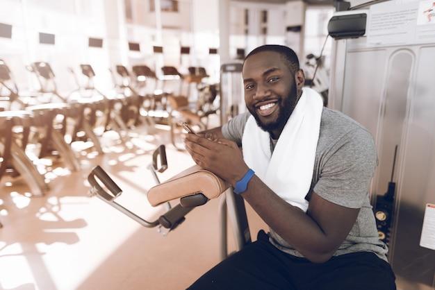 Een man met een moderne sportschool die na de training rust