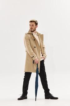 Een man met een modieuze kapselparaplu in zijn handen jas regenbescherming