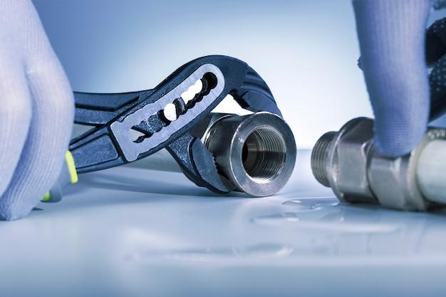 Een man met een moersleutel elimineert het lek in de pijp.